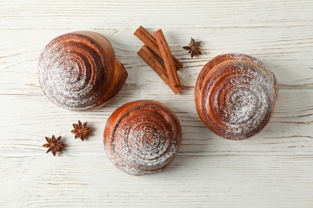 Rotoli di cannella con zucchero a velo e bastoncini di cannella sulla tavola di legno bianca