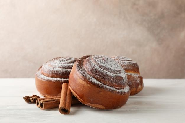 Rotoli di cannella con zucchero a velo e pile di cannella su bianco