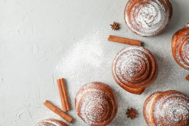 Rotoli di cannella con zucchero a velo e pile di cannella sul tavolo grigio