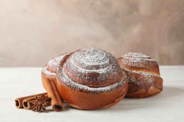 Rotoli di cannella con zucchero a velo e pile di cannella sulla tavola di legno bianca
