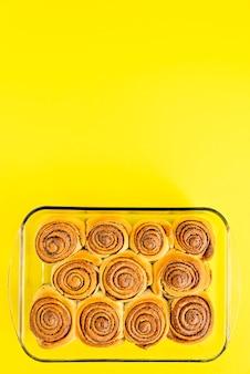 Rotoli di cannella di recente sostenuti dolci o cinabri su giallo