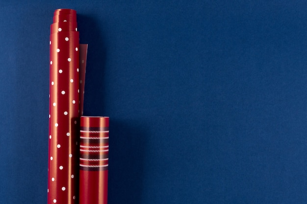 Rotoli di carta da imballaggio rossa su sfondo blu classico colore 2020. prepararsi per natale, san valentino 14 febbraio. piatto disteso, copia spazio, banner.