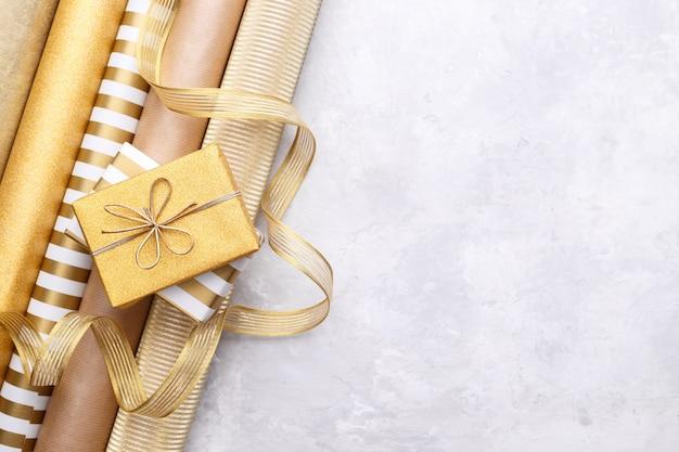 Rotoli di carta da regalo lucidi dorati e scatole regalo