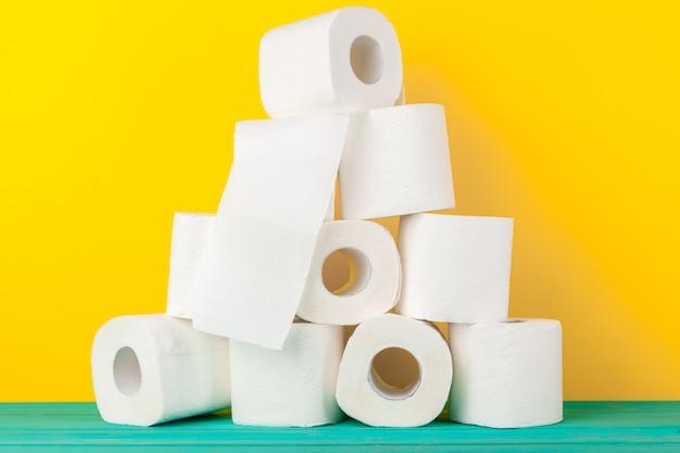 Rotoli di carta igienica impilati su sfondo giallo