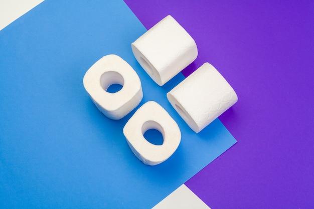 Rotoli di carta igienica spiegata sul blu. vista piana, vista dall'alto