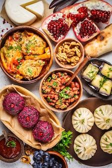 Rotoli di khinkali, phali, chakhokhbili, lobio, formaggio, melanzane sul tavolo bianco.