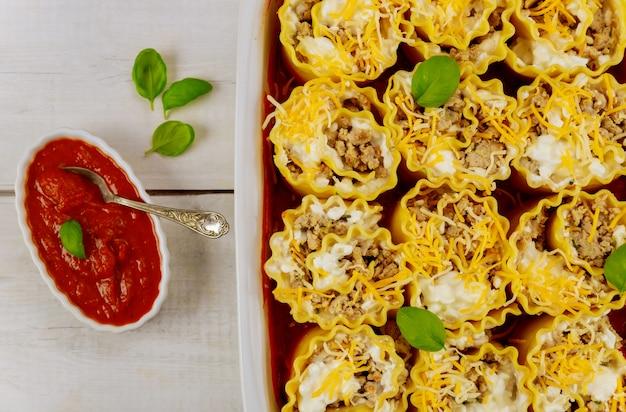 Rotoli di lasagne ripiene in teglia con salsa di pomodoro.