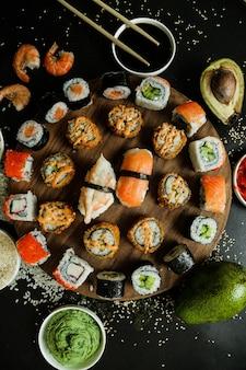 Rotoli di mix vista dall'alto su un supporto con salsa di soia wasabi zenzero avocado e semi di sesamo