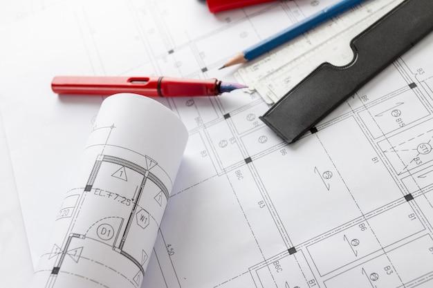 Rotoli di progetti di architettura e planimetrie sul tavolo e architetto strumenti di disegno.