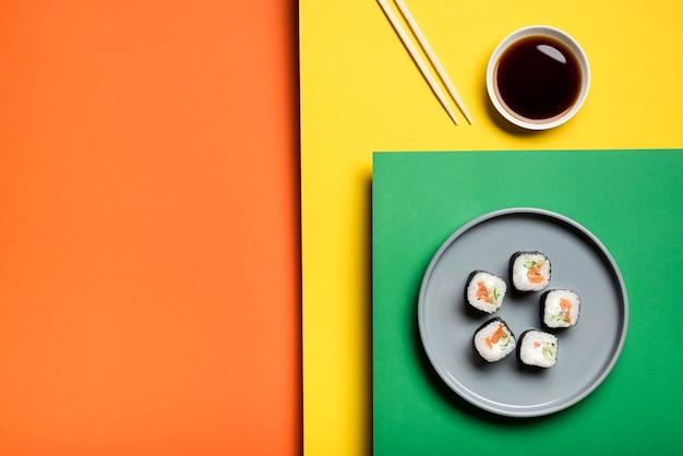 Rotoli di sushi asiatici tradizionali su fondo variopinto
