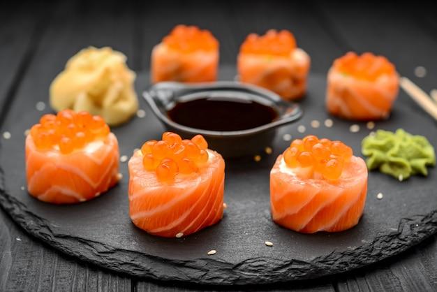 Rotoli di sushi di color salmone sul nero.