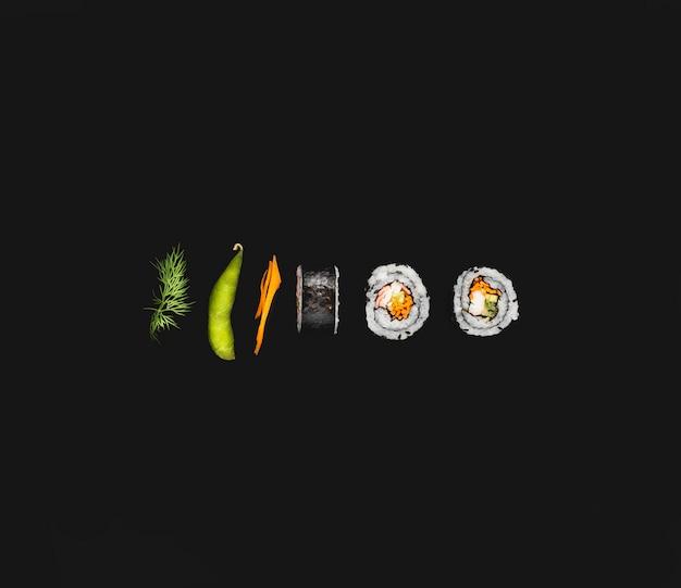 Rotoli di sushi di maki con edamame su fondo nero
