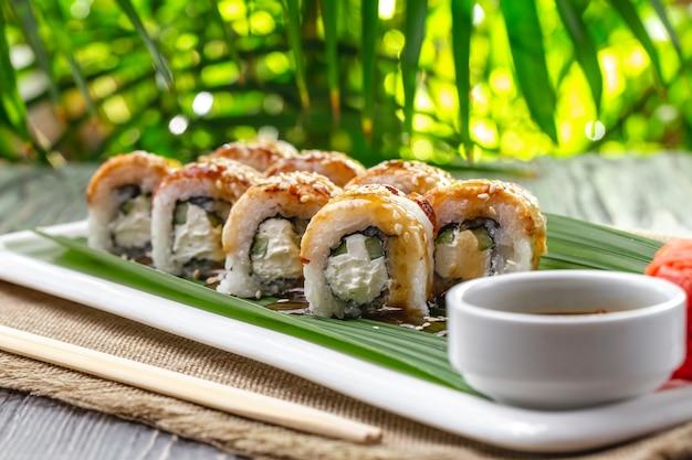 Rotoli di sushi di vista laterale con l'anguilla con wasabi allo zenzero e salsa di soia su un piatto