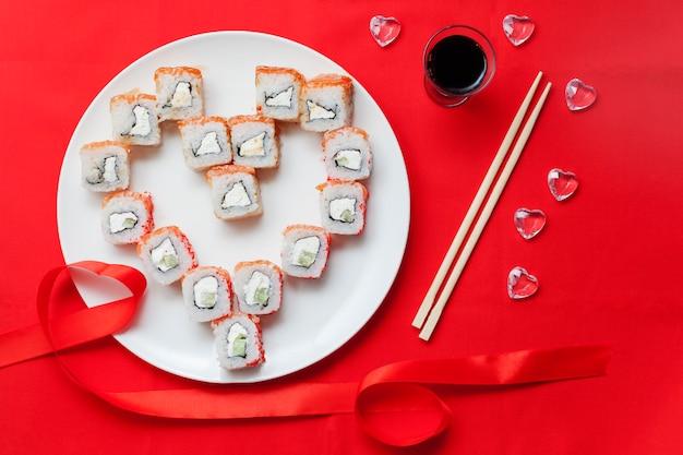 Rotoli di sushi disposti a forma di cuore su un piatto