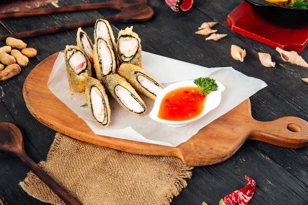 Rotoli di sushi fritti nel grasso bollente con i bastoncini di granchio agrodolci