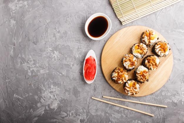 Rotoli di sushi giapponesi di maki con formaggio cremoso sul bordo di legno su calcestruzzo grigio