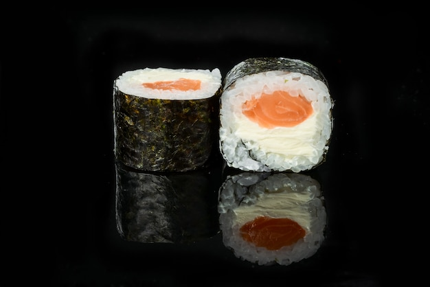 Rotoli di sushi giapponesi freschi tradizionali su un fondo nero