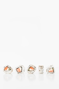 Rotoli di sushi giapponesi freschi tradizionali su una priorità bassa bianca