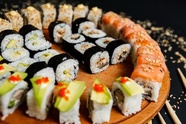 Rotoli di sushi mix vista laterale con semi di sesamo e bacchette di avocado su un supporto