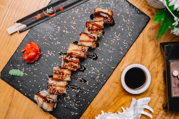 Rotoli di sushi vista dall'alto con anguilla con wasabi allo zenzero e salsa di soia