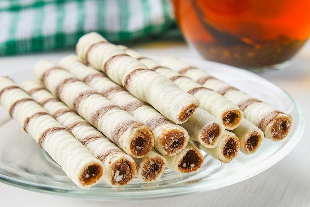 Rotoli di wafer a strisce, delizioso snack al cioccolato sul tavolo di legno bianco.