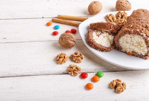 Rotoli il dolce con cagliata e le noci isolate su legno bianco