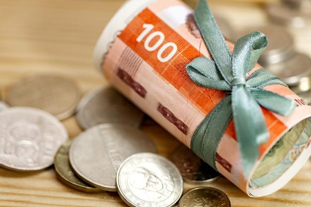 Rotoli la banconota e le monete dei soldi 100 sulla tavola di legno