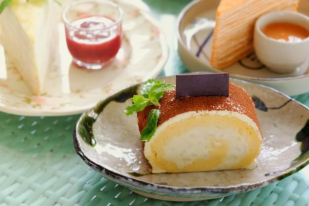 Rotoli la torta con polvere di cioccolato, un pezzo in piatto