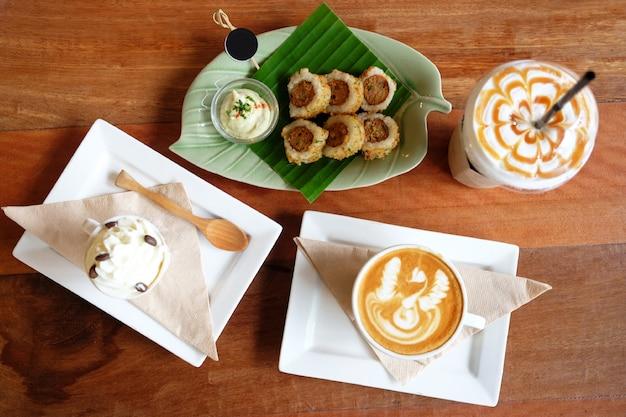 Rotoli tailandesi della carne di maiale della miscela del riso dei sushi con salsa sulla foglia della banana e panna montata su una tazza di latte caldo
