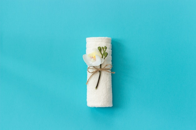Rotolo bianco del tovagliolo legato con la corda con il ramoscello del fiore dell'orchidea sul fondo della carta blu.