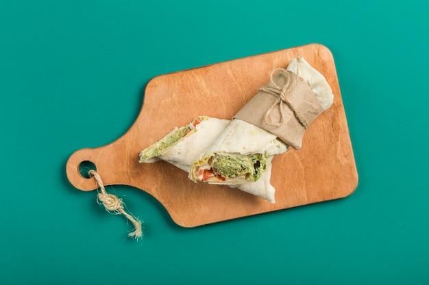 Rotolo con i falafel per una dieta vegetariana su una vista dall'alto di una tavola di legno con copyspace.