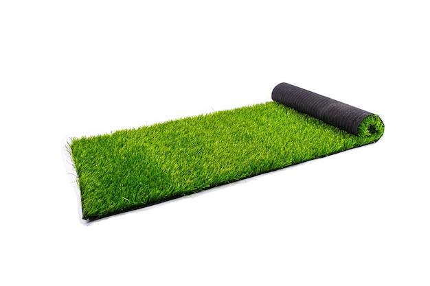Rotolo con prato verde artificiale isolato su sfondo bianco, copertura per parchi giochi e campi sportivi.