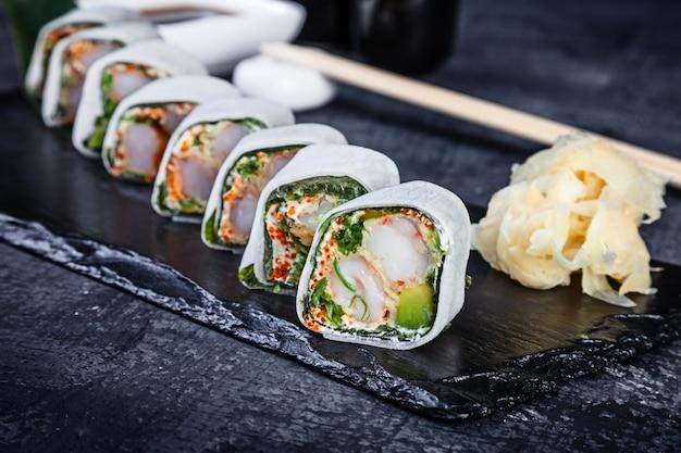 Rotolo daikon con gamberetti con gamberi e caviale tobico servito su lastra di pietra scura con salsa di soia e zenzero