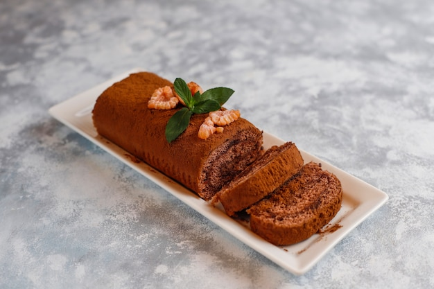 Rotolo del dolce di cioccolato con cacao in polvere sul piatto bianco, vista superiore