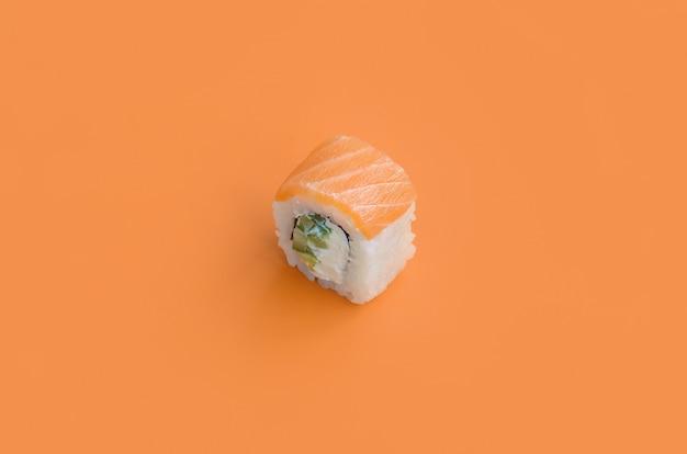 Rotolo di filadelfia con i salmoni su fondo arancio. vista dall'alto di minimalismo piatto con cibo giapponese