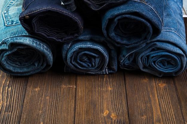 Rotolo di jeans sfilacciati o collezione di jeans blue jeans su legno scuro grezzo