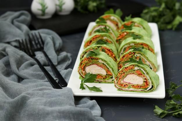 Rotolo di lavash con bastoncini di granchio, spinaci, prezzemolo e carote in stile coreano su un piatto contro una superficie scura