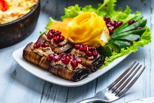 Rotolo di melanzane vista laterale alla griglia melanzane con noci melograno cetriolo e lattuga su un piatto