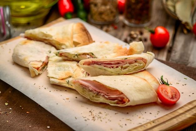 Rotolo di pane pita sandwich club sano con formaggio, prosciutto e prezzemolo