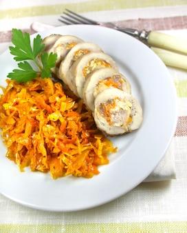 Rotolo di pollo con carota, formaggio e noci servito su un piatto con cavolo in umido