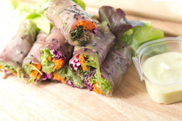 Rotolo di primavera fresca o rotolo di insalata mescolato con tonno carota vegetale sul tagliere.