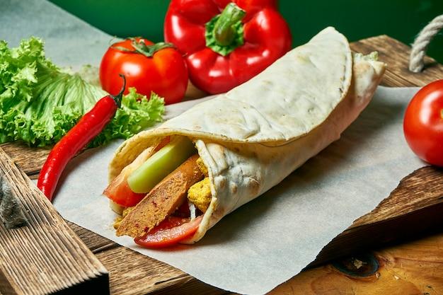 Rotolo di shawarma vegetariano in pita con salsiccia di soia, verdure e tofu fritto. cibo gustoso, sano e verde. cibo da strada vegano