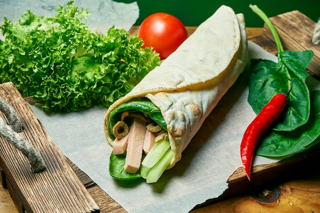 Rotolo di shawarma vegetariano in pita con spinaci, verdure, olive e carne di soia. cibo gustoso, sano e verde. cibo da strada vegano