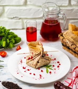 Rotolo di snack lavash con formaggio e semi di granato, pane, verdure e sorbetto su un piatto bianco. spuntino
