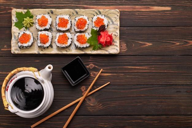 Rotolo di sushi con caviale rosso su un piatto con wasabi, zenzero, foglie di acero e bacchette per sushi, su uno sfondo di legno, vista dall'alto