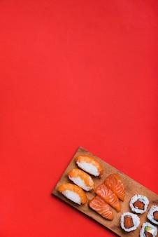 Rotolo di sushi con salmone sul tagliere contro sfondo rosso
