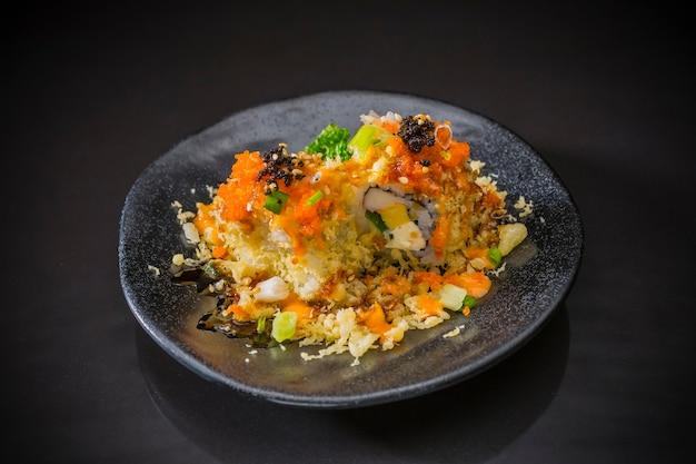 Rotolo di sushi con salmone, uovo dolce e tempura, cucina giapponese, messa a fuoco selettiva