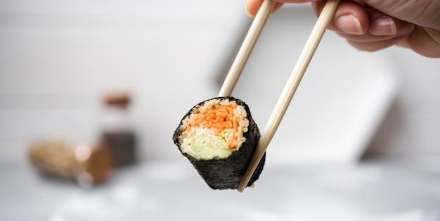 Rotolo di sushi del primo piano con le verdure tenute in bacchette