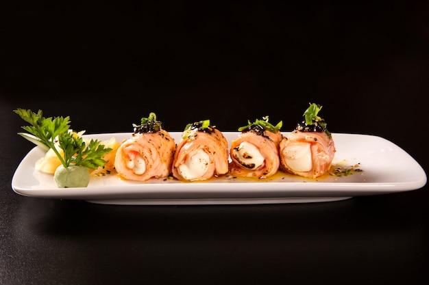 Rotolo di sushi delizioso di philadelphia con salmone arrostito e crema di formaggio.
