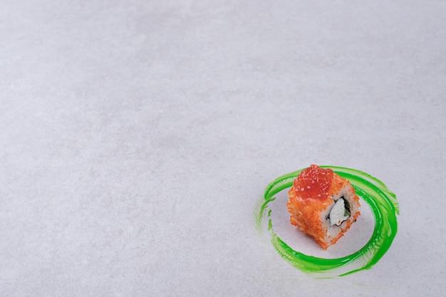 Rotolo di sushi della california su priorità bassa bianca con anello di plastica verde.